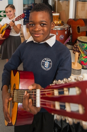 Pupil playing guitar at St Philip's CE Primary School
