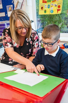 Pupil getting help from a teacher at St Philips CE Primary School